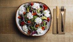 Ensalada de verduras con verduras verdes de cebolla y salsa de crema servida en el plato sobre mesa de madera - foto de stock