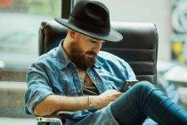 Giovane barbuto bell'uomo in cappello e camicia di jeans navigando pensieroso sul telefono cellulare seduto in poltrona nera — Foto stock