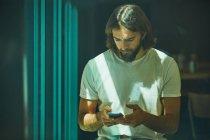 Giovane uomo bello barbuto appoggiato al muro con il telefono cellulare in mano premurosamente sms — Foto stock