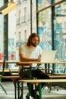 Joven hombre guapo barbudo sentado en la cafetería exterior y trabajando con el ordenador portátil en la mesa - foto de stock