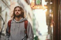 Giovane uomo bello barbuto in felpa grigia con cappuccio e zaino che cammina seriamente fuori — Foto stock