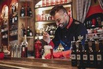 Barista sorridente in uniforme e guanto rosso preparare cocktail fumante — Foto stock
