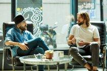 Bello uomo in cappello nero seduto e godendo di conversazione con un amico in possesso di una tazza di caffè in caffè — Foto stock