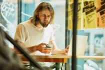 Молодой бородатый красивый мужчина сидит в кафе и работает, держа телефон и ноутбук на столе — стоковое фото