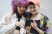 Young attractive women with black and pink hair in bright clothes laughing and embracing while watching on mobile phone on grey background — Stock Photo