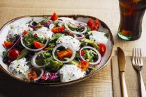 Vegetable salad with onion greens and cream sauce served on plate on wooden table — Foto stock