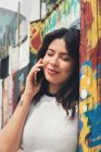 Smiling young woman talking phone near graffiti wall — Stock Photo