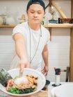 Giovane uomo in piedi in cucina e la consegna di ciotola con fresco cucinato piatto giapponese — Foto stock