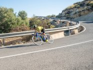 Здорова людина їзда на велосипеді по гірській дорозі в сонячний день — стокове фото