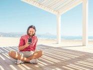 Uomo barbuto smartphone di navigazione mentre seduto in gazebo sulla spiaggia di sabbia vicino al mare nella giornata di sole — Foto stock