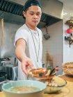 Мультирасовый мужчина готовит японское блюдо под названием рамен в азиатском ресторане в помещении — стоковое фото