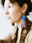 Seitenansicht der attraktiven verträumten jungen Brünette mit hellen handgefertigten Ohrring aus bunten Fäden — Stockfoto