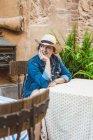 Жінка в солом'яному капелюсі і одязі, сидячи на терасі ресторану в середньовічному місті — стокове фото