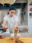 Молодой человек кладет горячую лапшу в миску палочками для еды во время приготовления японского блюда на кухне — стоковое фото