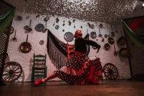 Натхненний жіночий танцюрист в яскравій фламенко спідниці виконавського танцю пози в етнічній кімнаті з антикварними предметами на стіні — стокове фото