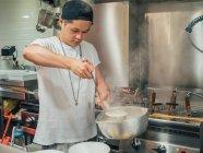Junger Mann mit schwarzer Mütze gießt heiße Brühe aus Topf für japanisches Gericht namens Ramen in asiatischem Café — Stockfoto