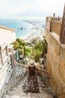 Unerkennbare Frau im Sommer-Outfit steht auf einer Steintreppe mit Meeresküste im Hintergrund — Stockfoto