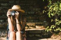 Путешествуя женщина в платье и шляпе с помощью камеры, сидя на каменных ступенях на солнечной улице — стоковое фото