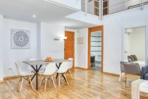 Interior of simple stylish dining room and stairs in modern duplex flat in daylight — Stock Photo
