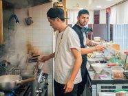 Seitenansicht von multirassischen jungen Männern, die in einem asiatischen Restaurant japanisches Gericht namens Ramen kochen und in die Kamera schauen — Stockfoto