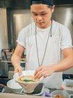 Азиатский мужчина кладет половину яйца в миску со свежим вареным раменом на кухне ресторана — стоковое фото