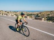 Здорова людина їзда на велосипеді по гірських прибережних дорогах в сонячний день — стокове фото