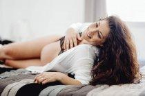 Щаслива вагітна жінка в нижній білизні лежачи на ліжку — стокове фото