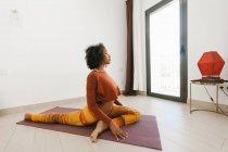 Afro-americano attraente giovane donna seduta in posa yoga con gli occhi chiusi sul tappeto nella stanza della luce — Foto stock