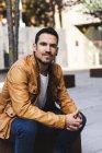 Fiducioso ragazzo alla moda seduto sulla strada — Foto stock