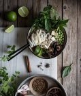 Served Pho soup with noodles on marble board on wooden table with spices — Stock Photo