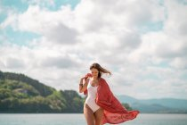 Smiling young woman in swimsuit posing with scarf on beach — Stock Photo