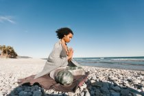 African American young woman meditating in lotus yoga posture on sandy beach in bright day — Stock Photo