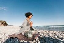 Афроамериканець молода жінка розмірковуючи в поставі Lotus йоги на піщаному пляжі в світлий день — стокове фото