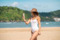 Улыбающаяся молодая женщина в купальнике и шляпе с помощью смартфона на пляже — стоковое фото