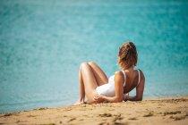 Femme en maillot de bain assis sur une plage de sable et regardant la vue — Photo de stock