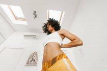 Afro-américain attrayant jeune femme effectuant posture de yoga avec les mains derrière le dos dans la salle de lumière — Photo de stock