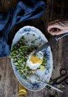 Degustación de manos humanas de plato servido con guisantes verdes salteados y huevo frito en mesa de madera - foto de stock