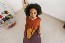 Лицо афроамериканской девушки, сидящей в позе йоги с закрытыми глазами на коврике в светлой комнате — стоковое фото