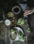 De cima mão de pessoa irreconhecível que faz torradas com pate de caju verde e partes de pepino na tábua de madeira — Fotografia de Stock
