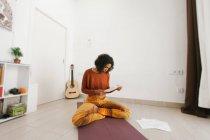 Afro-americano attraente giovane donna seduta con le gambe incrociate e controllare i documenti di routine — Foto stock