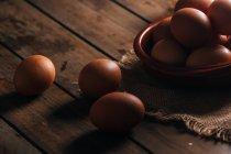 Курячі яйця з мискою та мішками на дерев'яному столі — стокове фото