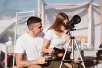 Novia elegante sentado en el novio vuelta y mirando a través del telescopio en el cielo cerca del hotel burbuja - foto de stock