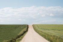 Estrada abandonada que vai acima entre grandes prados verdes no verão no fundo do céu azul — Fotografia de Stock