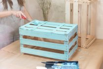 Closeup of woman paining wooden box in blue color with roller — Stock Photo