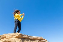 Young brunette woman taking photo with smartphone while standing on sandstone cliff against blue sky background — Stock Photo