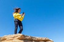 Jeune femme brune prenant des photos avec smartphone tout en se tenant debout sur une falaise de grès sur fond de ciel bleu — Photo de stock