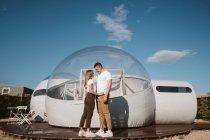 Боковой вид страстного мужчины и молодой женщины, стоя перед романтическим прозрачным гламурным гламуром — стоковое фото