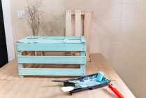 Freshly painted wooden box and tools on table — Stock Photo