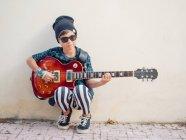 Cheeky ragazzo eccitato attivo in vestiti colorati suonare la chitarra, appoggiato sullo sfondo della parete bianca — Foto stock
