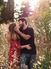 Nachdenklicher Mann umarmt lächelnde schwangere Frau im Hintergrund des malerischen grünen Parks bei sonnigem Tag — Stockfoto